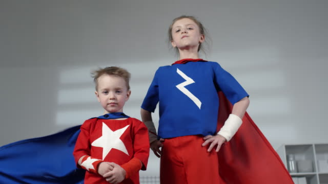 Little Brother and Sister in Superhero Costumes Posing for Camera - vídeo