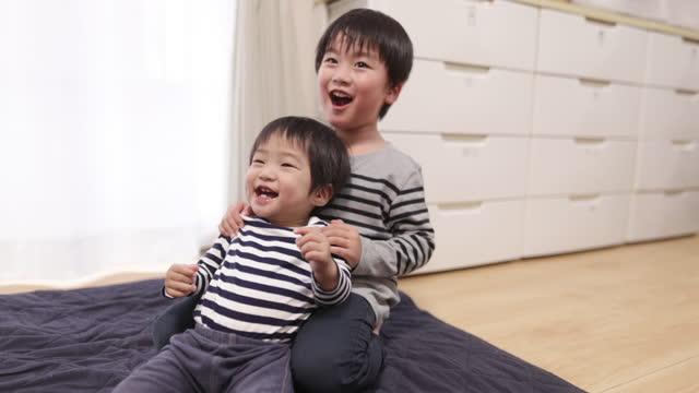 リビングルームで一緒に遊ぶ弟 - 兄弟姉妹点の映像素材/bロール