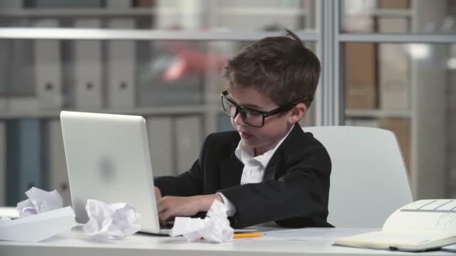 vidéos et rushes de petit génie d'affaires - costume habillé
