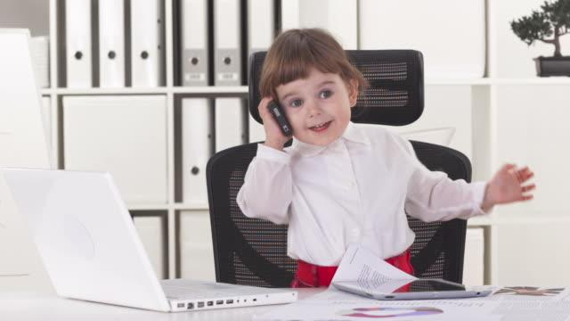 hd: маленький бизнес-леди разговаривает по телефону - только одна девочка стоковые видео и кадры b-roll