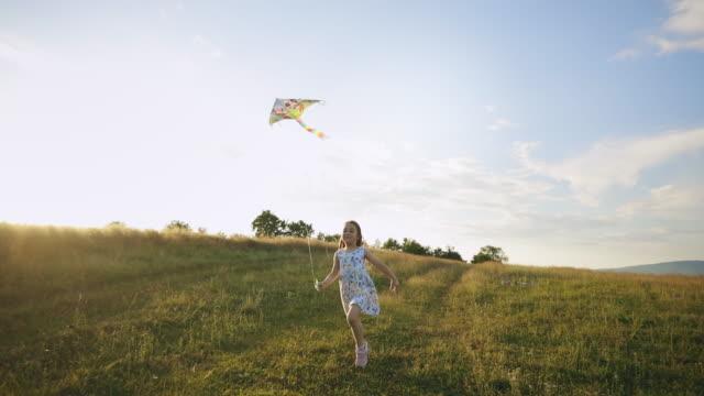 Little carefree girl flying a kite