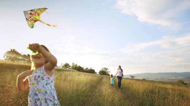 Little cheerful girl flying a kite