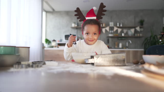 Little Chef Little african ethnicity girl making Christmas cookies. christmas fun stock videos & royalty-free footage