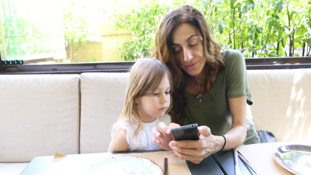 little child and mother in restaurant watching mobile video