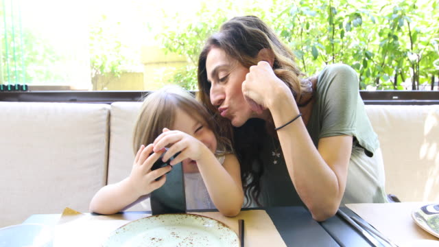 little child and mother watching mobile and speaking in restaurant video