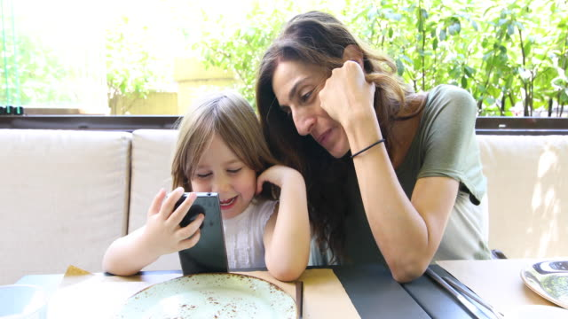 little child and mother watching mobile in restaurant video