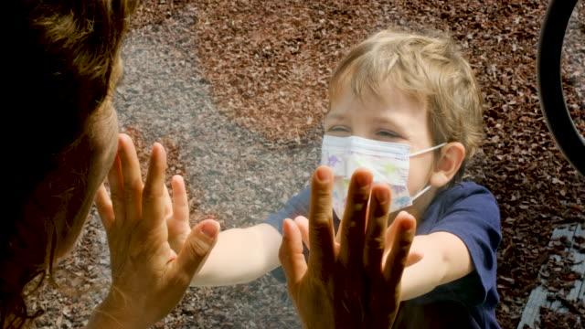 彼の居心地の良い-19隔離されたママが窓のガラスで分離されているのを見ている小さな子供の男の子 - 分離点の映像素材/bロール