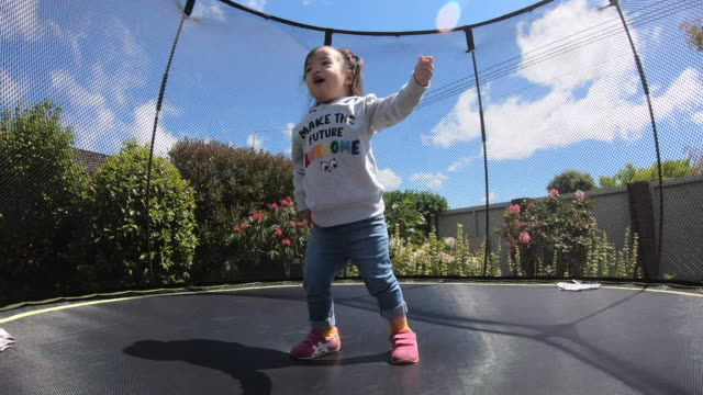 Little child enjoys jumping on trampoline