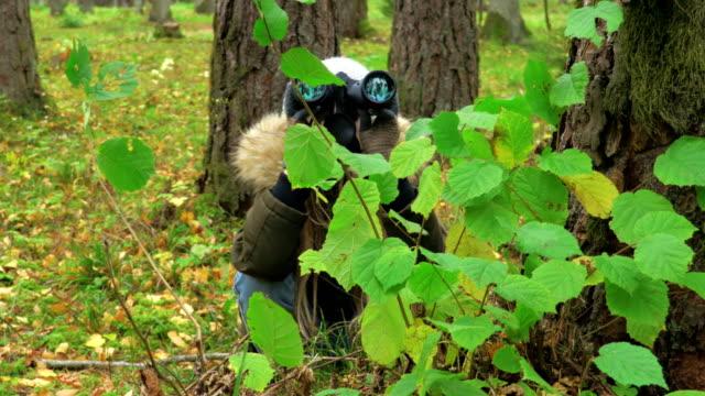 Little child girl behind the tree near bush looking through binoculars.Explorer and adventure concept - vídeo