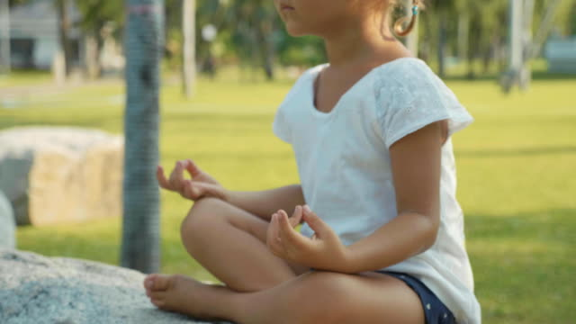 little child girl meditating in beautiful park with palm trees on the background - gambe incrociate video stock e b–roll