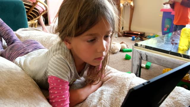 liten barnflicka med en elektronisk tablett - ligga på mage bildbanksvideor och videomaterial från bakom kulisserna