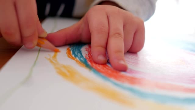 vídeos de stock e filmes b-roll de little child hands painting, drawing rainbow pattern - produto artístico