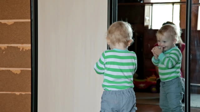 Little child have fun, play with ball near mirror video