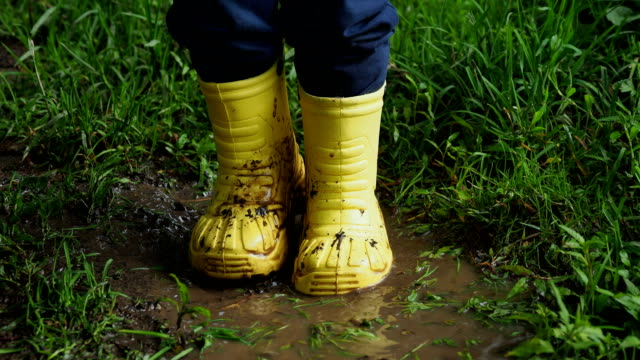 Little child in bright yellow rubber boots splashing in a puddle. Kid's feet protected from dirty water