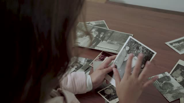 A little child is looking at old vintage photos of her family and dad FDV