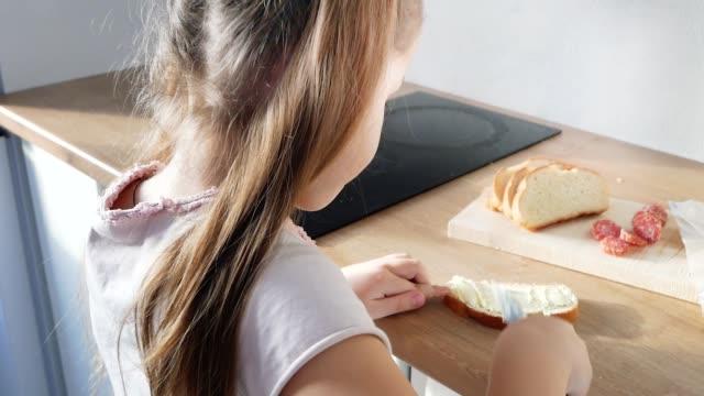 vídeos de stock, filmes e b-roll de criança fazendo sanduíche com manteiga e linguiça - gordura