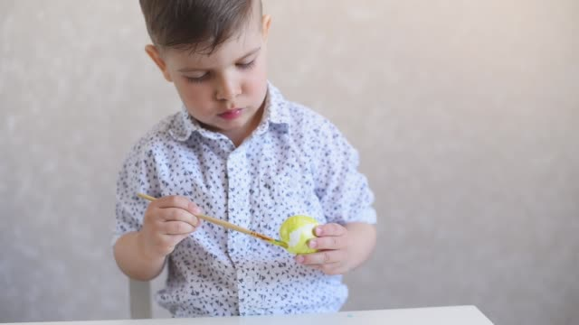 a little child paints an one easter egg at the table on a white background. - abbigliamento da neonato video stock e b–roll