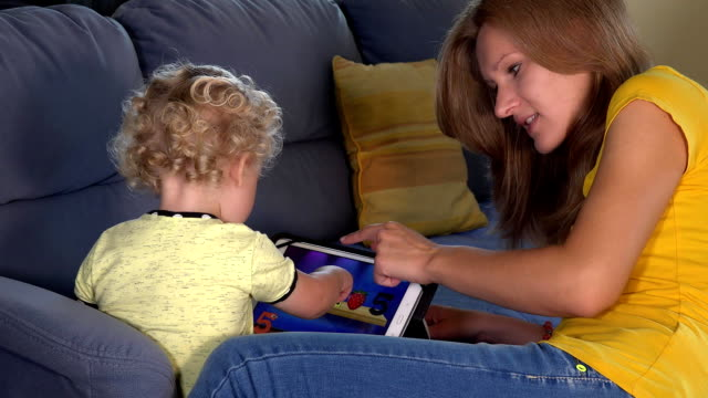 Little child playing with tablet computer and mother give her hive five video
