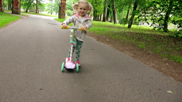 Little child ride scooter in park on summer day. Cute girl play outdoors video