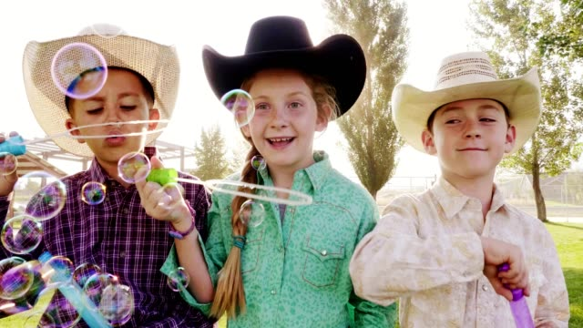 little children blowing bubbles - cowboy video stock e b–roll