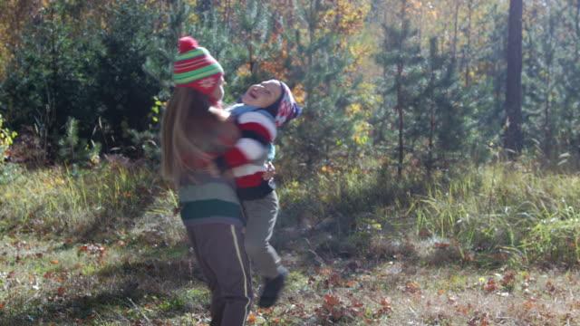 小さな子どもがあり、兄と妹の遊びと秋の森ではしゃぐ - 兄弟姉妹点の映像素材/bロール