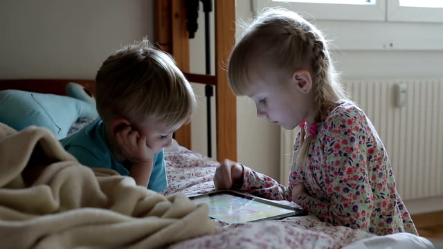 Little children play games on tablet in the bed and smile. video