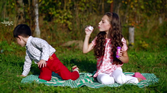 Little children playing in the garden with soap bubbles video