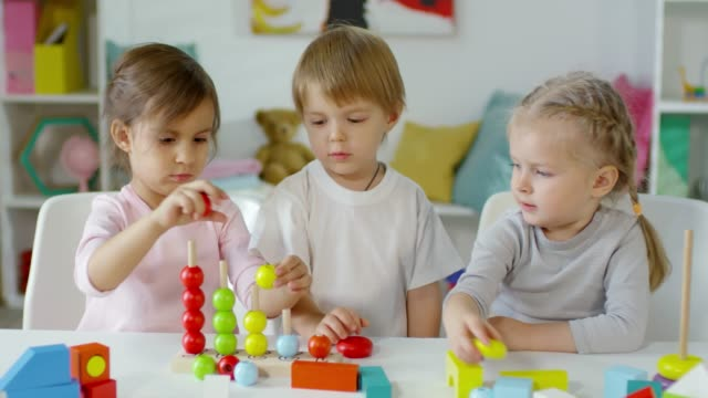 Little Children Playing with Toy at Table in Kindergarten Two little caucasian girls and cute boy playing together with educational toy at table in kindergarten child care stock videos & royalty-free footage