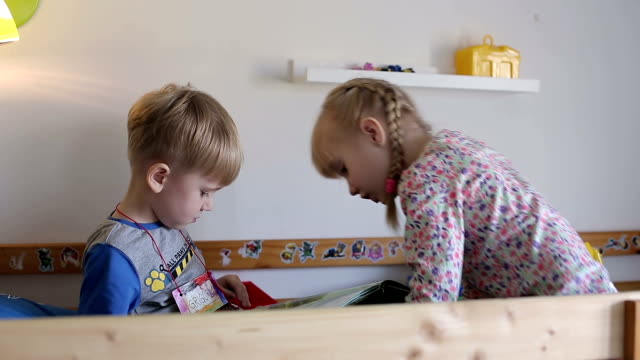 Little children read a book in the bed. video