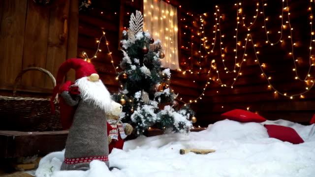 Kleiner Weihnachtsbaum im Schnee in der Nähe ein Haus mit Girlanden geschmückt. Parallaxe – Video
