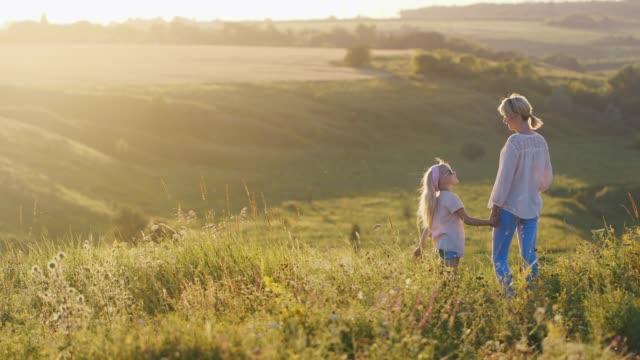 金髪のクールな少女が緑のフィールド上美しい夕日を mom を示しています ビデオ