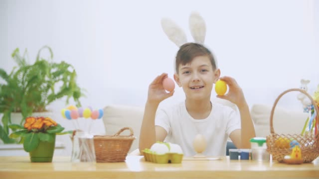 Little cute and adorable boy is smiling and playing with colorful chicken's eggs in his hands. Concept Easter holiday.