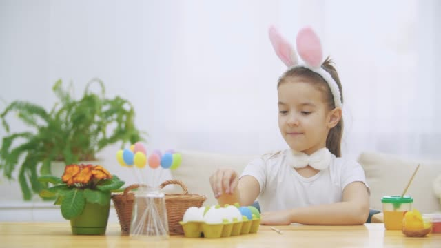 Little cute and adorable girl is smiling sincerely. She takes an Easter egg from the basket and looking at it. Girl is waving with her liitle flat of hand. Concept Easter holiday.