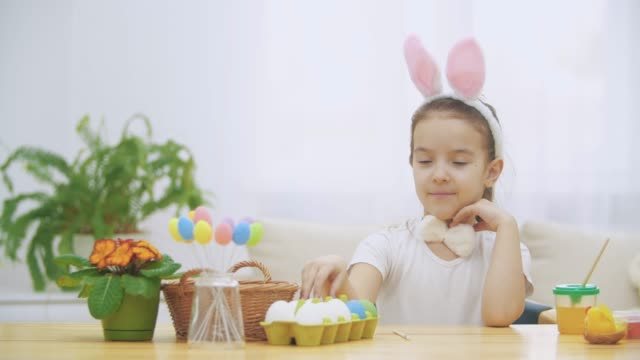 Little cute and adorable girl is smiling sincerely. She takes an Easter egg from the basket and looking at it, then pointing on it. Concept Easter holiday.
