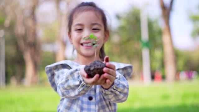 vídeos de stock, filmes e b-roll de a menina asiática bonito pequena dá a planta pequena à matriz, excepto o conceito da terra. - assistindo