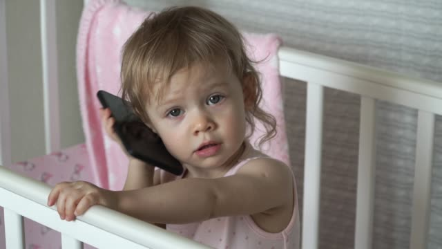 kleine niedliche babymädchen ruft per mobiltelefon und lächelnd - menschlicher kopf stock-videos und b-roll-filmmaterial