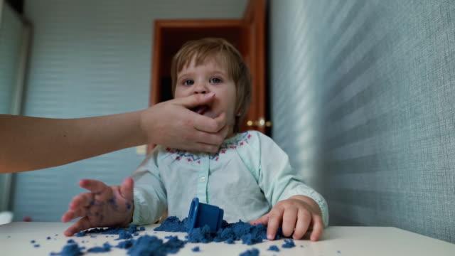 vídeos de stock e filmes b-roll de little cute baby girl licks her hands, soiled by kinetic sand in slow motion - boca suja