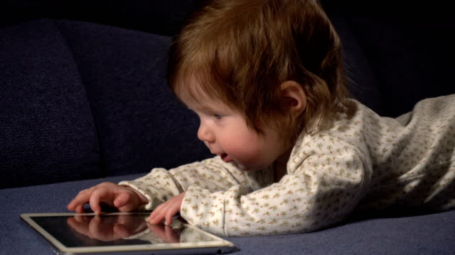 Little cute baby girl playing with touchpad video