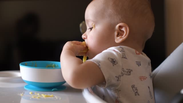 Little cute boy happily eating baby porridge with his hands and genuinely smiles Little cute boy happily eating baby porridge with his hands and genuinely smiles. Kid claps hands soiled with porridge desire stock videos & royalty-free footage