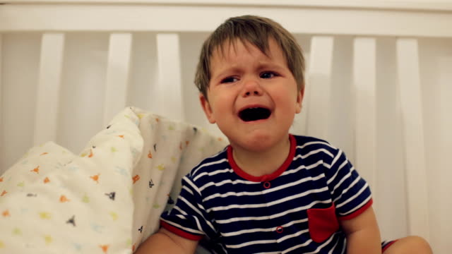 Little cute boy wearing blue striped pijama crying in the bed video
