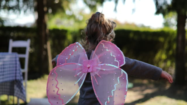 Little cute butterfly A cute little girl wearing butterfly costume wings flying through the yard fairy stock videos & royalty-free footage