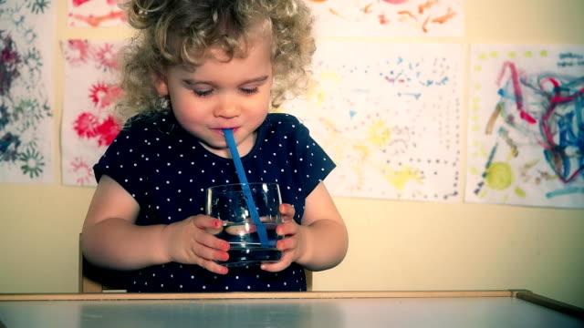 stockvideo's en b-roll-footage met kleine schattige kind blaaslucht met rietje in het glas met water - stro