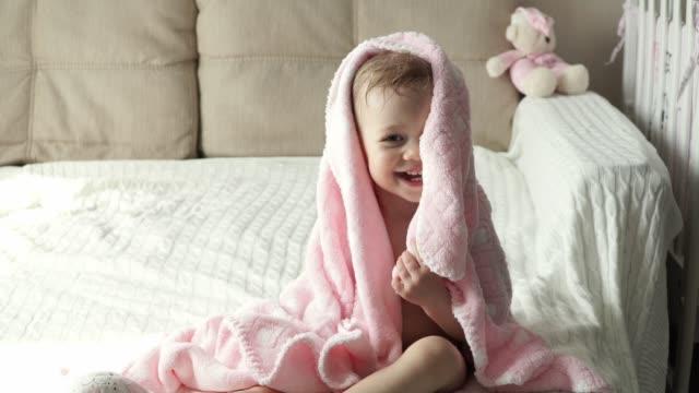 lilla söta tjejen efter bad sitter leker med en handduk och skrattar - människohuvud bildbanksvideor och videomaterial från bakom kulisserna