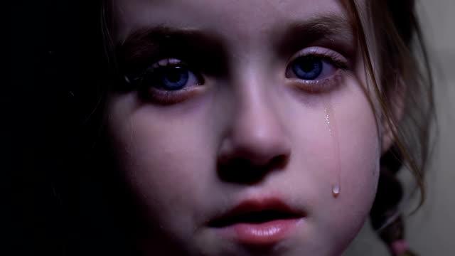 liten söt flicka gråter desperat, kränkningar av barnets rättigheter, försvarslös unge - förskoleelev bildbanksvideor och videomaterial från bakom kulisserna
