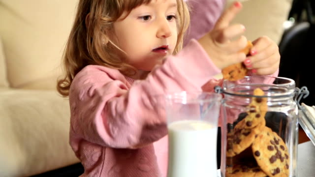 Little cute girl eating cookie video