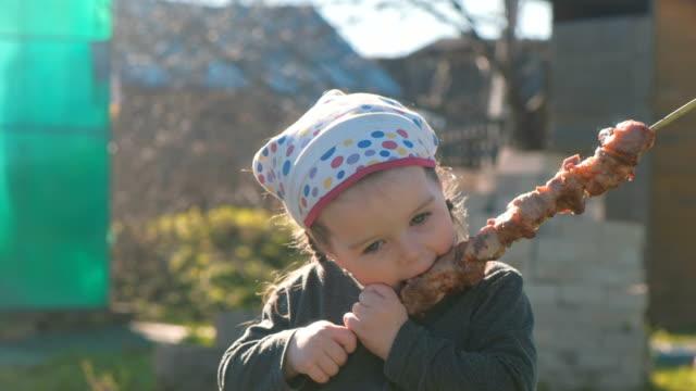 かわいい女の子は、串バーベキュー シャシリクを食べる。 - ブタ点の映像素材/bロール