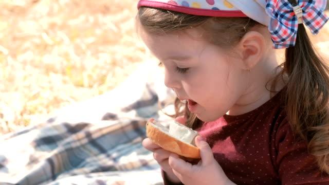 lilla söta tjejen äter smörgås med bröd och smältost. familj picknick. slickar hennes smutsiga fingrar. - cheese sandwich bildbanksvideor och videomaterial från bakom kulisserna