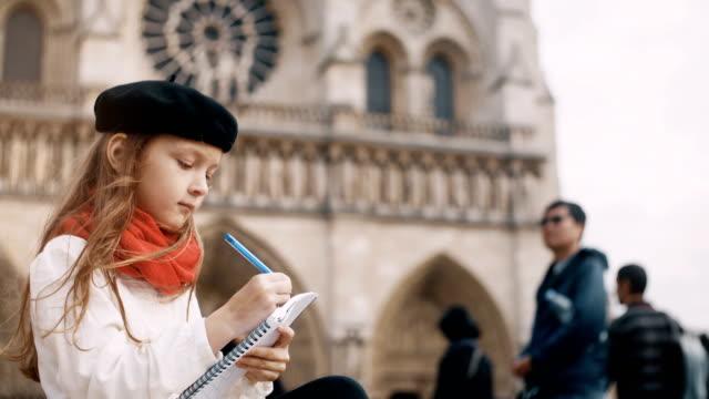 vídeos de stock, filmes e b-roll de menina bonita lenço boina e vermelho sentado perto da notre dame e desenhando o esboço em paris, frança - moda parisiense