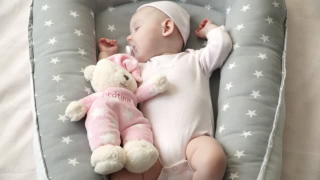 little cute girl in pink clothes sleeping in a cocoon crib - ciuccio video stock e b–roll