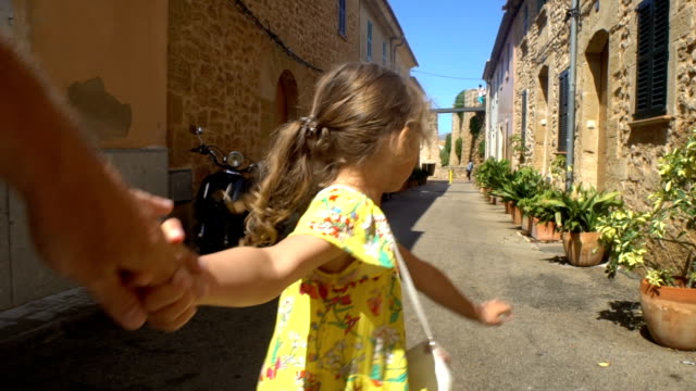 Little Cute Girl Leading Parent to the Adventure in an Old European Town Follow me. Little Cute Girl Leading Parent to the Adventure in an Old European Town. european culture stock videos & royalty-free footage